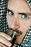 A portrait of a young Arab Man wearing a kaffiyeh Dirinkling coffee. Model Release Available