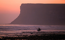 © Licensed to London News Pictures.28/10/15<br /> Saltburn, UK. <br /> <br /> A surfer heads out for a dawn session as the pink early morning light spreads over the beach at Saltburn in Cleveland. <br /> <br /> Photo credit : Ian Forsyth/LNP