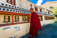 A monk turns prayer wheels at he circumambulates around the Diskit Monastery, Nubra Valley, Ladakh, Jammu and Kashmir State, India.