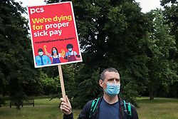 A PCS member holds a placard at a picket outside the Old Police House in Hyde Park by Royal Parks workers outsourced via French multinational VINCI Facilities as part of joint strike action by the United Voices of the World (UVW) and Public and Commercial Services (PCS) trade unions on 30th July 2021 in London, United Kingdom. The joint strike, with members dual carding over pay, conditions and the sacking of a member of staff, is believed to be the first between a TUC and a non-TUC trade union and follows the launch of a legal challenge by the Royal Parks workers against indirect racial discrimination by the Royal Parks.
