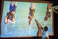 """Merrick, New York, USA. 11th June 2017.  """"American Grit"""" contestant CHRIS EDOM (wearing white T-shirt), 48, of Merrick, hosts backyard Viewing Party for Season 2 premiere. Edom walked up to large screen and pointed to contestants hanging upside down over water in first edurance challenge, as his guests watched Episode 1 of FOX network reality television series broadcast that Sunday night outdoors."""
