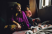 A Muslim Roma woman at the window with her grandson. Roma Gypsies caught between the frontlines during the Balkan wars. Near Travnik, Bosnia Spring 1994...Roma Gypsies left Rajasthan in India a thousand years ago, in the ninth and tenth centuries. They were pushed west by the Ottoman Muslim Empire as it moved through Persia towards the frontiers of Europe. They entered Europe in the foutrteenth century and were slaves in Romania and Moldavia until the mid 1850s. There are about 15 million Roma gypries in the world, about 12 million who live in Europe. they are Europe's largest ethnic minority. They have rich traditions and culture, their own language. They are renowned for their prowess in music and dance; they are also skilled craftsman, metal roofmakers, silver and goldsmiths. Their traveling and nomadic lifestyle which grew from a necessity to find work, and because they were often moved on from one place to the next, has given them both a liberty but also marks them as different and they are often feared by sedentary peoples, who label and scapegoat them. They are hardy survivors and live in the brunt of racism and prejudice, often marginalised, living in poverty, without proper human rights afforded to them..