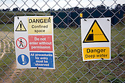 Danger deep water signs on sewage works fence
