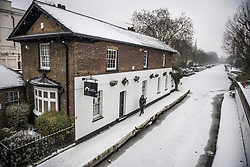 © Licensed to London News Pictures. 02/03/2018. London, UK. A man walks along the tow path of the Grand Union Canal as further snowfall covers the landscape in Little Venice, Westminster, London. The 'Beast from the East' and Storm Emma have brought extreme cold, ice and heavy snow to the UK. Photo credit: Ben Cawthra/LNP
