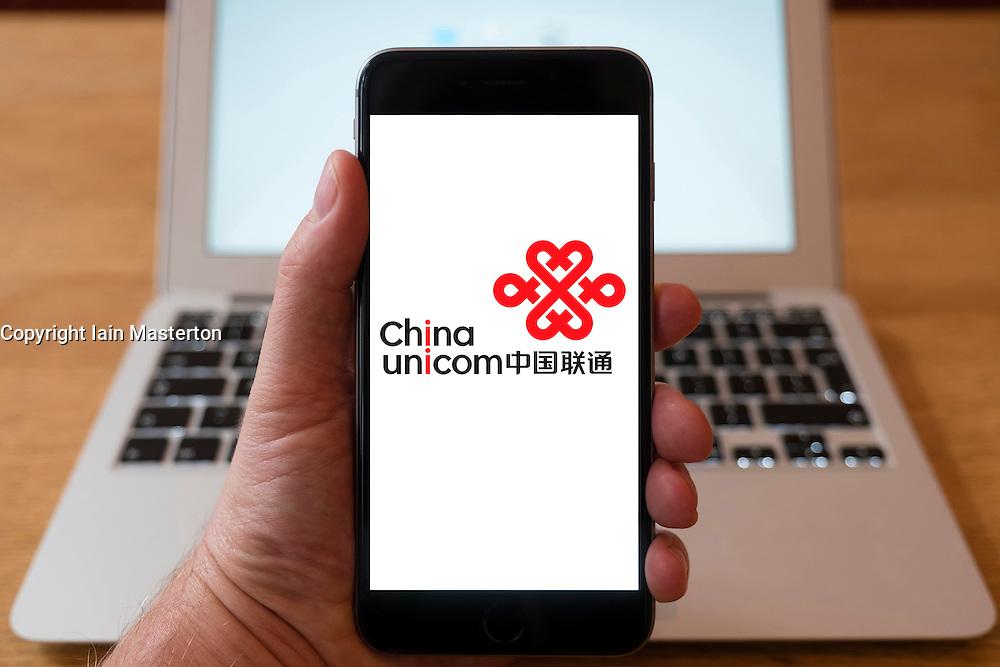 Using iPhone smartphone to display logo of China Unicom, Chinese state-owned telecommunications operator.
