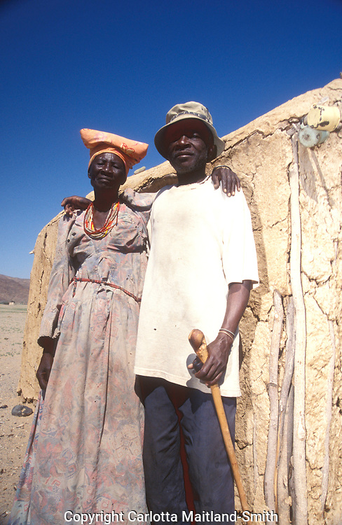 Elderly couple in Purros village in Kaokoveld region north west Namibia Africa...The Herero's dress, consisting of several layers and, once married, a 'cow horn' head dress, derives from Victorian-era German missionaries who took exception to what they considered a lack of modesty among the local women..