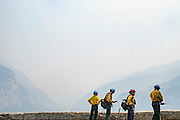 Firefighters near Tunnel View take a moment after cutting of the fire's fuel at Yosemite National Park during the Ferguson Fire on Wednesday, Aug. 8, 2018, in Mariposa County, Calif.