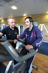 A young man with learning disabilities works out in a gym; helped by a sports instructor as part of a Sport Ability Day North Yorkshire,