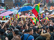 23 JUNE 2016 - MAHACHAI, SAMUT SAKHON, THAILAND: People wait in a driving rainstorm to see Aung San Suu Kyi after her visit to the Burmese community in Samut Sakhon, a province south of Bangkok. Tens of thousands of Burmese migrant workers, most employed in the Thai fishing industry, live in Samut Sakhon. Aung San Suu Kyi, the Foreign Minister and State Counsellor for the government of Myanmar (a role similar to that of Prime Minister or a head of government), is on a state visit to Thailand. Even though she and her party won the 2015 elections by a landslide, she is constitutionally prohibited from becoming the President due to a clause in the constitution as her late husband and children are foreign citizens        PHOTO BY JACK KURTZ