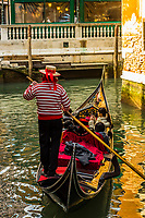 A gondolier rowing on a back canal, Venice, Italy.