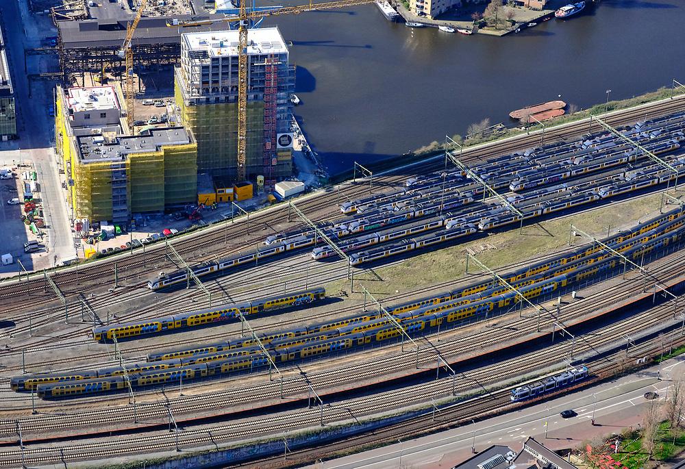 Nederland, Noord-Holland, Amsterdam; 23-03-2020; Rietlanden, emplacement van de NS. Piet Heinkade. Omdat de NS een speciale basisdienstregeling ingevoerd heeft ivm de Corna-crisis zijn veel treinen 'geparkeerd' op opstelsporen. Op de foto intercity treinen en Sprinters, dubbeldek treinen.<br /> Railway yard of the NS. Because the NS has introduced a special basic timetable in connection with the Corna crisis, many trains have been 'parked' on sidings.<br /> <br /> luchtfoto (toeslag op standaard tarieven);<br /> aerial photo (additional fee required)<br /> copyright © 2020 foto/photo Siebe Swart