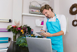 Mid adult man taking order of flowers