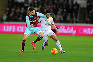 Neil Taylor of Swansea city ® is challenged by Carl Jenkinson of West Ham Utd. Barclays Premier league match, Swansea city v West Ham Utd at the Liberty Stadium in Swansea, South Wales  on Sunday 20th December 2015.<br /> pic by  Andrew Orchard, Andrew Orchard sports photography.