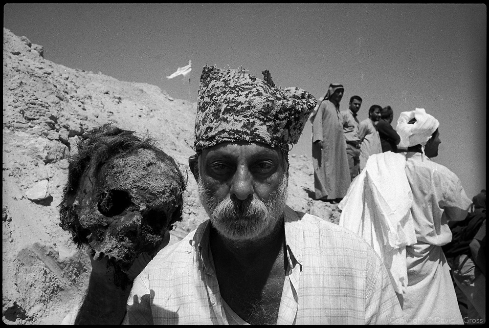 A man posed with a skull in a mass grave near Al-Musayab, Iraq. When the diggers saw him do this, they chased him out of the grave.
