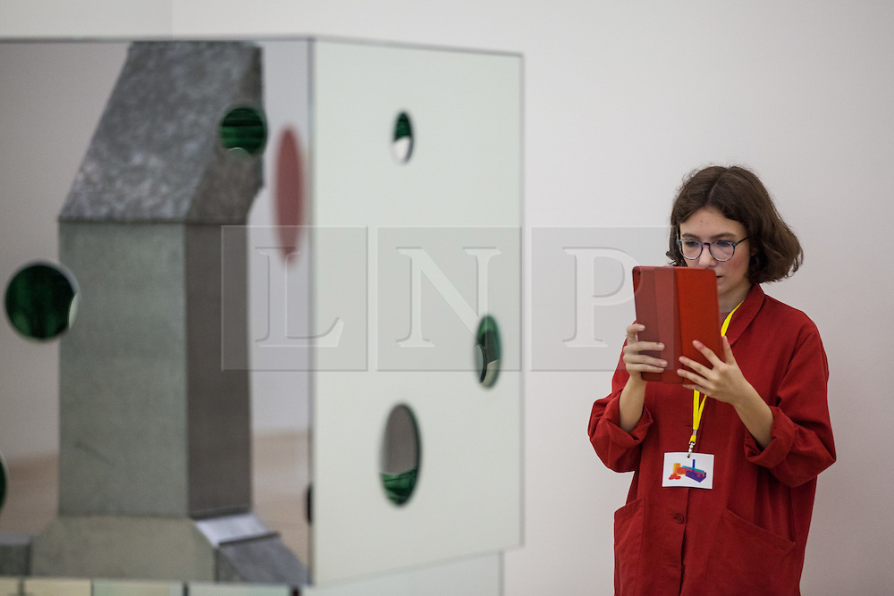 © Licensed to London News Pictures. 14/06/2016. London, UK. A woman takes a photograph of 'The Passing Winter' by Yayoi Kusama, on display in the Switch House, the new Tate Modern building which opens to the public on Friday 17 June 2016. The ten-storey extension was designed by architects Herzog & de Meuron and includes the world's first gallery space dedicated exclusively to live art, film and installations. Photo credit: Rob Pinney/LNP