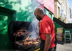 © Licensed to London News Pictures. 23/08/2019. London, UK. Jerk chicken being prepared ahead of the 2018 Notting Hill Carnival which starts this weekend. Warm weather is expected over the bank holiday weekend with carnival attracting over 1 million people to the capital. Photo credit: Ben Cawthra/LNP
