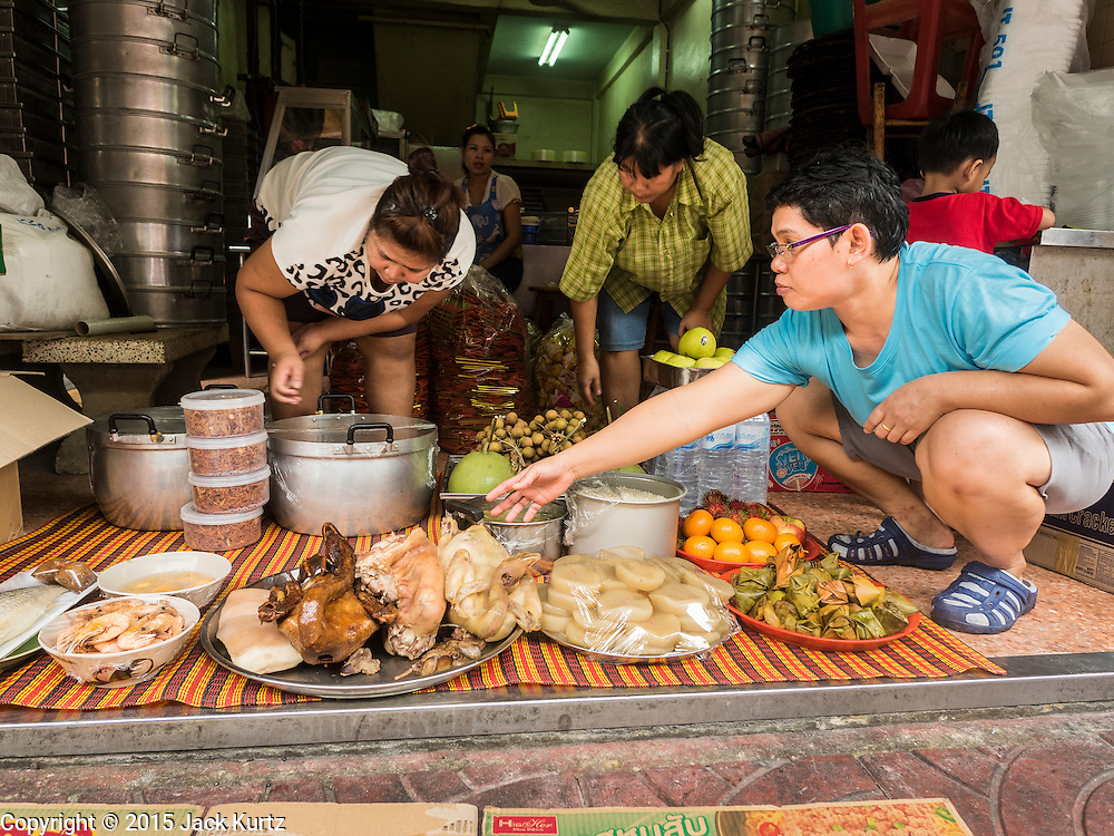 28 AUGUST 2015 - BANGKOK, THAILAND:  Women leave out a banquet of food for their ancestors on Hungry Ghost Day in Bangkok's Chinatown. Mahayana  Buddhists believe that the gates of hell are opened on the full moon of the seventh lunar month of the Chinese calendar, and the spirits of hungry ghosts allowed to roam the earth. These ghosts need food and merit to find their way back to their own. People help by offering food, paper money, candles and flowers, making merit of their own in the process. Hungry Ghost Day is observed in communities with a large ethnic Chinese population, like Bangkok's Chinatown.      PHOTO BY JACK KURTZ