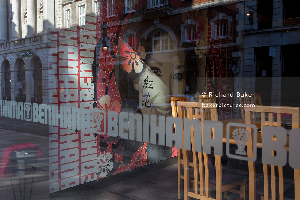 With a further 154 covid deaths reported in the last 24hrs, bringing the total to 43,081 in the UK during the Coronavirus pandemic, the smiling Asian face and empty seating through the window of the still closed Benihana sushi and Japanese steakhouse restaurant on Sackville Street off Piccadilly, on 24th June 2020, in London, England. Prime Minister Boris Johnson is however allowing restaurants to re-open on the 4th July.