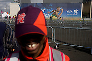 A Games Maker volunteer with a gold tooth and passing spectators near a Usain Bolt Visa billboard during the London 2012 Olympic Park during the games. London 2012 volunteers are called 'Games Makers', as they are helping to make the Games happen. Up to 70,000 Games Makers take on a wide variety of roles across the venues: from welcoming visitors; to transporting athletes; to helping out behind the scenes in the Technology team to make sure the results get displayed as quickly and accurately as possible. Games Makers come from a diverse range of communities and backgrounds, from across the UK and abroad. The vast majority are giving up at least 10 days to volunteer during the Games.