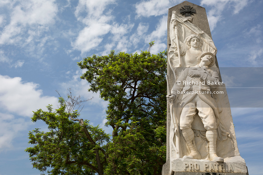 """The WW1 war memorial with the Latin Pro Patria inscription on the main Le Promenade street, on 22nd May, 2017, in Lagrasse, Languedoc-Rousillon, south of France. Pro Patria is a line from the Roman lyrical poet Horace's Odes, translated as: """"It is sweet and proper to die for the fatherland."""" Lagrasse is listed as one of France's most beautiful villages and lies on the famous Route 20 wine route in the Basses-Corbieres region dating to the 13th century."""