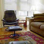 A large black leather chair and footrest in front of two bright windows, with one large venetian blind mostly obscuring them. There is a large Asian style carpet covering most of the floor, and a large sofa on the right,  a lamp behind it is on in the corner.