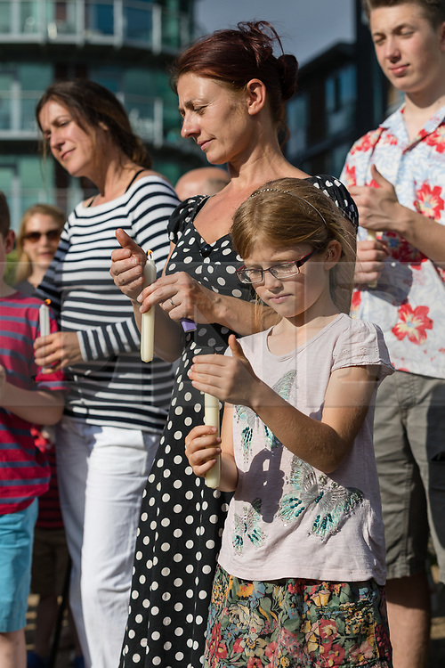 © Licensed to London News Pictures. 16/06/2017. LONDON, UK.  People hold candles at The Great Get Together. Neighbours and friends of Jo Cox attend The Great Get Together near Hermitage Moorings in Wapping to pay tribute and celebrate Jo's call that more unites us than divides us on the anniversary of her death. Jo Cox lived on a house boat in Wapping with her husband Brendan Cox and two children. Photo credit: Vickie Flores/LNP