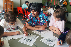 Junior school teacher and pupils working at desk in classroom,