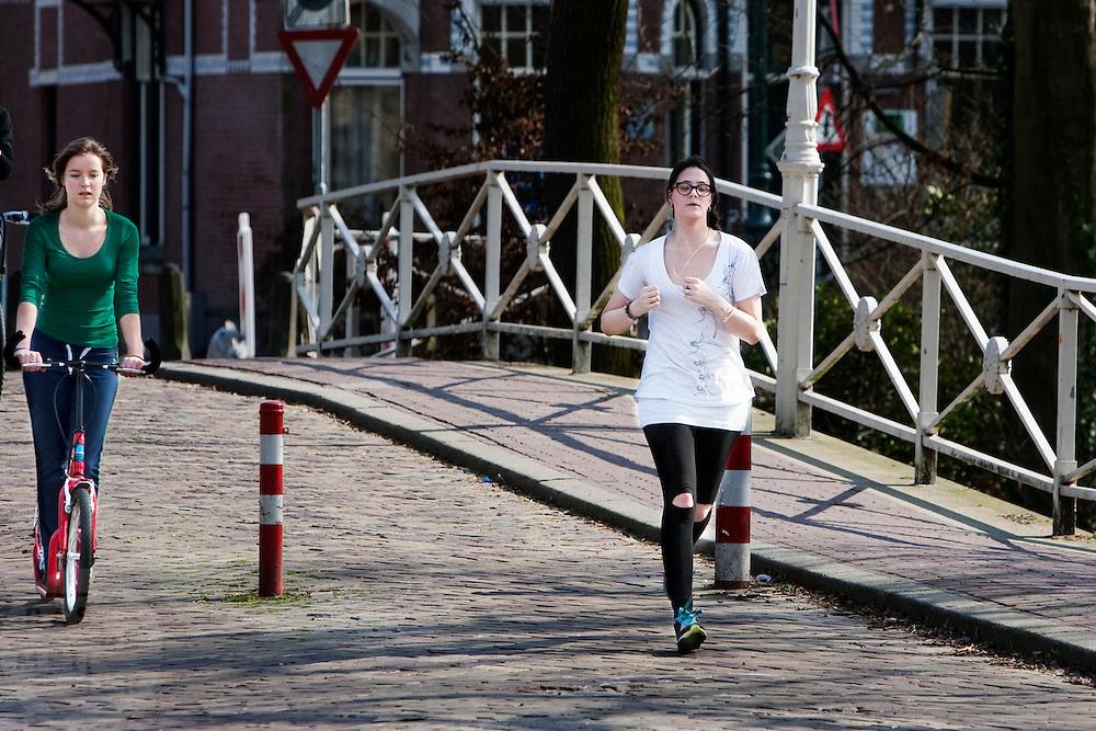 Een meisje is aan het hardlopen in Utrecht. Ze wordt begeleid door een meisje op een step