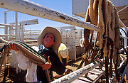 14 APRIL 2002 - CAVE CREEK, ARIZONA, USA: A  boy hangs flank straps for the bucking horses behind the bucking chutes at the Cave Creek Fiesta Days Rodeo in Cave Creek, Arizona, April 14, 2002.  PHOTO BY JACK KURTZ