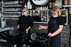 © Licensed to London News Pictures. 07/10/2020. London, UK. Hairdressers wearing face coverings in a beauty salon in Leyton, East London hold a mixer tap as the salon experiencing no water following a water main pipe burst in Hackney Marshes on Tuesday. Photo credit: Dinendra Haria/LNP