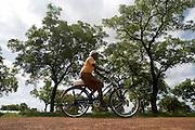 Fajima Yakaba, 12, drives her UNICEF-donated bicycle along the road leading to her village as she heads back home after school in Savelugu, Ghana on Tuesday June 5, 2007..