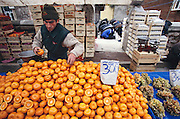 On Friday, the noon prayers have begun and a vendor arranges his oranges while behind him men pray at a small mosque. Hungry Planet: What the World Eats (p. 258). This image is featured alongside the Çelik family images in Hungry Planet: What the World Eats.
