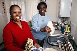 Carer helping elderly woman with washing up,