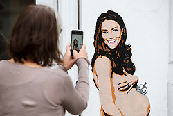 © Licensed to London News Pictures. 13/11/2014. LONDON, UK. A woman takes a picture of a spray-painted picture of the pregnant Duchess of Cambridge, naked with a miniature crown balancing on her belly, made by graffiti artist Pegasus on a wall in Islington, north London. Photo credit : Tolga Akmen/LNP