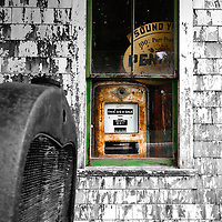 Abandoned Esso gas filling station along the country road in Waite, Maine.  Old gas pump and Pennzoil sign in window.
