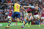 Philippe Senderos of Aston Villa has his shirt tugged by Lukas Podolski of Arsenal. Barclays Premier league match, Aston Villa v Arsenal at Villa Park in Birmingham on Saturday 20th Sept 2014<br /> pic by Mark Hawkins, Andrew Orchard sports photography.