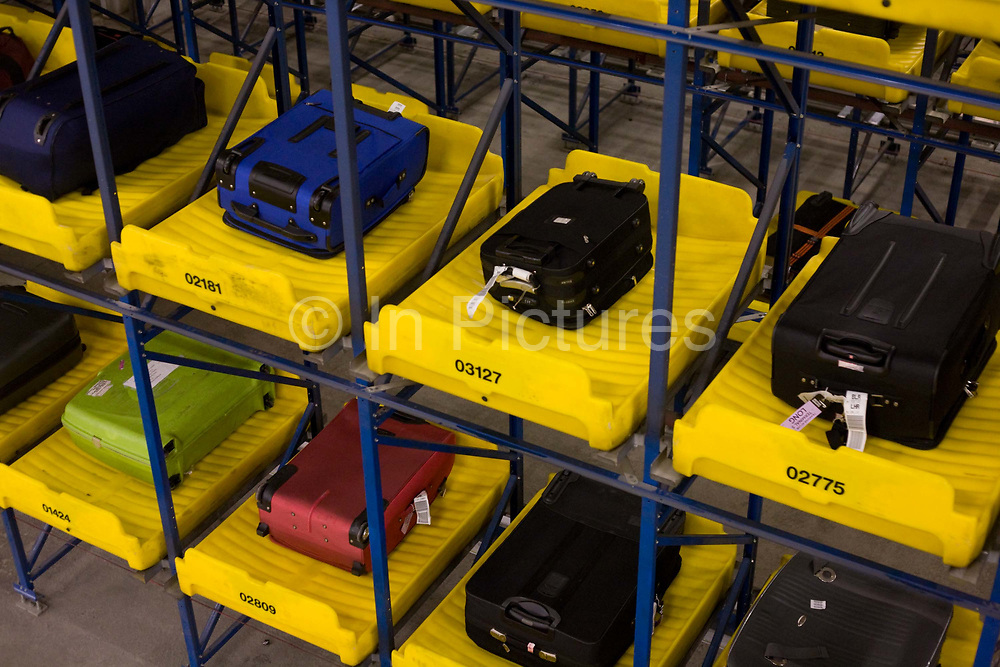 """50-70,000 pieces of British Airways baggage a day travel through 11 miles of conveyor belts which were installed in a 5-storey underground hall beneath the 400m (a quarter of a mile) length of Terminal 5 at Heathrow Airport. Here we see items of luggage spending 4 hours in transit, held in a fully-automated parking lot for bags. Computers decide when to fish the item out and re-introduce it into the system and load it on to the appropriate aircraft. T5 alone has the capacity to serve around 30 million passengers a year and was completed in 2008 at a cost of £4.3bn. The system was designed by an integrated team from the airport operator BAA, BA and Vanderlande Industries of the Netherlands, and handles both intra-terminal and inter-terminal luggage. From writer Alain de Botton's book project """"A Week at the Airport: A Heathrow Diary"""" (2009)."""