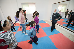 17 February 2020, Zarqa, Jordan: Incentive-Based Volunteer Lojain from Syria leads a Zumba session for children at the Lutheran World Federation community centre in Zarqa. Through a variety of activities, the Lutheran World Federation community centre in Zarqa serves to offer psychosocial support and strengthen social cohesion between Syrian, Iraqi and other refugees in Jordan and their host communities.