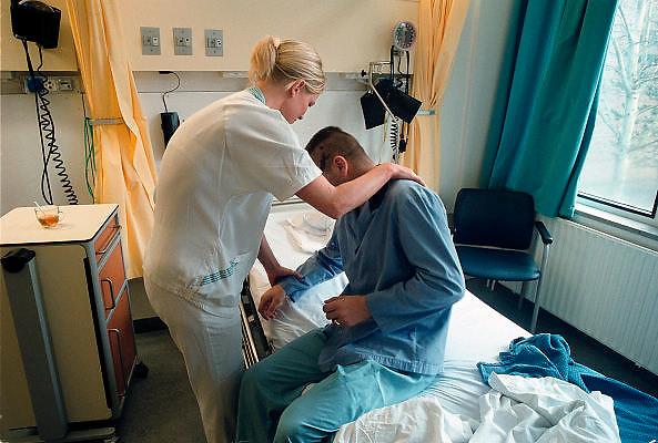 Nederland, Nijmegen, 3-5-2003..Verpleegkundige helpt patient. gezondheidszorg, patientenzorg, ziekteverzuim, ziektewet, zieke werknemer, gewond door ongeluk, letselschade. Personeelstekort...Foto: Flip Franssen