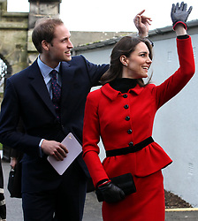 Prince William and Kate Middleton wave as they pass St Salvator's halls, during a visit to St Andrews University.