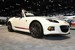"08  February 2013: 2013 Mazda MX-5 Miata roadster automobile. Chicago Auto Show, Chicago Automobile Trade Association (CATA), McCormick Place, Chicago Illinois<br /> <br /> 2013 MAZDA MX-5 MIATA: Since the Mazda MX-5 Miata first debut at the Chicago Auto Show (CAS) more than 20 years ago, this pure sports car continues to be the segment-defining roadster. With more than 900,000 units sold, the MX-5 is the best-selling two-seat roadster in the world. For the '13 model year, which is the third and current generation, the MX-5 wears an updated rendition of the original long, lean and supplely rounded body. Trim levels comprise the entry Sport, luxury-loaded Grand Touring, and in between those two, the all-new Club trim that replaces the previous Touring package. All 2013 MX-5 Miata models receive a fresh new front fascia, with fog lights and new 17-inch alloy wheel design on specific models. The thrilling growl when the ignition key is turned to start, comes from the MZR 2.0-liter DOHC four-cylinder. That engine produces 158 horsepower when equipped to the six-speed Sport automatic transmission with steering wheel mounted dual-paddle shifters, and 167hp with the manual gearbox. Either set-up is geared toward the joy of uncomplicated driving that is focused on the occupant behind the steering wheel. Sun worshipers have their choice of two distinctive and easy-to-operate roof covers. Standard is the Z-fold design soft top, and an available power retractable hardtop, which outsells the soft-tops by a 4:1 ratio worldwide. Mazda cleverly timed the opening-and-closing cycles for the hardtop at 12 seconds, which coincidently, is ""faster than the never-convenient red-light-green-light pause."" The top itself descends into a cleverly designed storage well, yet leaves the 5.3 cubic feet of cargo space completely untouched."