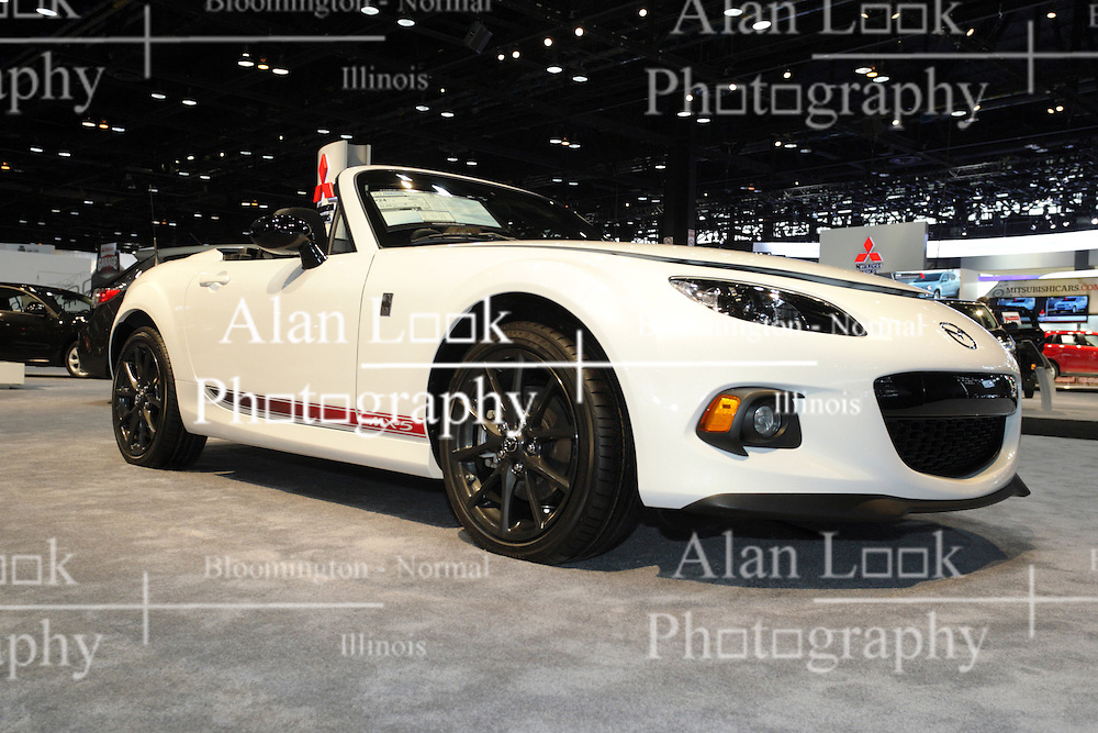 """08  February 2013: 2013 Mazda MX-5 Miata roadster automobile. Chicago Auto Show, Chicago Automobile Trade Association (CATA), McCormick Place, Chicago Illinois<br /> <br /> 2013 MAZDA MX-5 MIATA: Since the Mazda MX-5 Miata first debut at the Chicago Auto Show (CAS) more than 20 years ago, this pure sports car continues to be the segment-defining roadster. With more than 900,000 units sold, the MX-5 is the best-selling two-seat roadster in the world. For the '13 model year, which is the third and current generation, the MX-5 wears an updated rendition of the original long, lean and supplely rounded body. Trim levels comprise the entry Sport, luxury-loaded Grand Touring, and in between those two, the all-new Club trim that replaces the previous Touring package. All 2013 MX-5 Miata models receive a fresh new front fascia, with fog lights and new 17-inch alloy wheel design on specific models. The thrilling growl when the ignition key is turned to start, comes from the MZR 2.0-liter DOHC four-cylinder. That engine produces 158 horsepower when equipped to the six-speed Sport automatic transmission with steering wheel mounted dual-paddle shifters, and 167hp with the manual gearbox. Either set-up is geared toward the joy of uncomplicated driving that is focused on the occupant behind the steering wheel. Sun worshipers have their choice of two distinctive and easy-to-operate roof covers. Standard is the Z-fold design soft top, and an available power retractable hardtop, which outsells the soft-tops by a 4:1 ratio worldwide. Mazda cleverly timed the opening-and-closing cycles for the hardtop at 12 seconds, which coincidently, is """"faster than the never-convenient red-light-green-light pause."""" The top itself descends into a cleverly designed storage well, yet leaves the 5.3 cubic feet of cargo space completely untouched."""