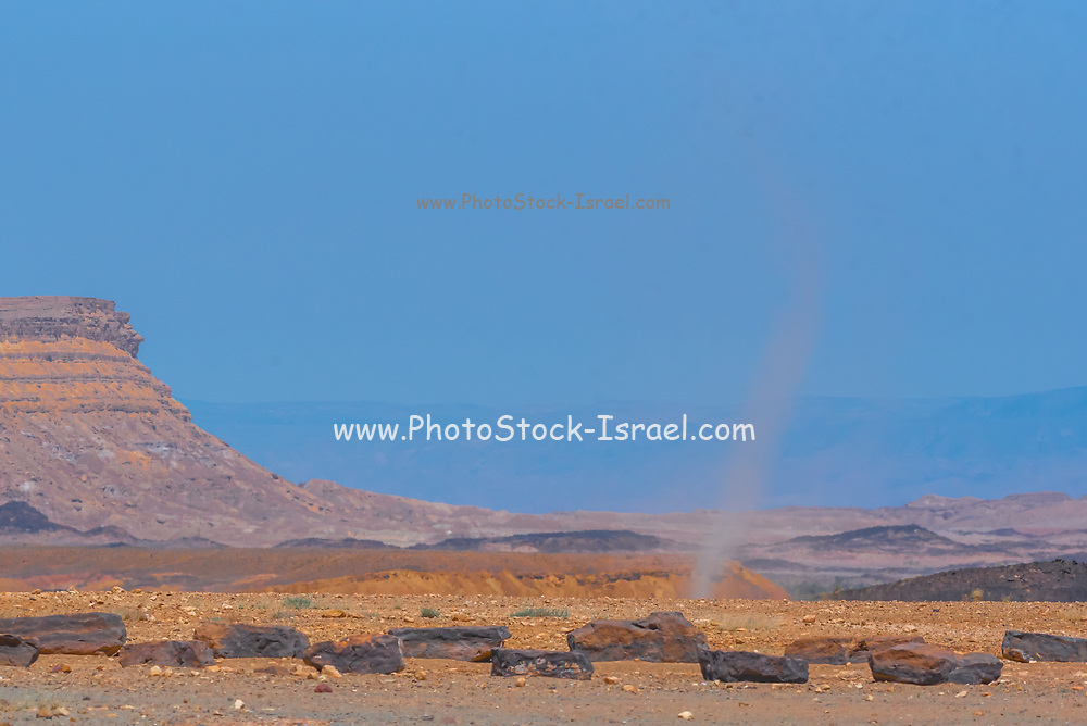 Whirlwind forms a dust pillar in the desert. Photographed in the Negev Desert, Israel
