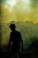 Smoke from burning crops fills the air behind a silhouetted man walking in a field along the banks of the Red River, Hanoi, Vietnam, Southeast Asia.