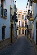 Historic buildings narrow Tenorio street in the old city, Ronda, Spain