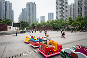A man sits on a childrens ride waiting for customers at an affordable housing neighbourhood in Chongqing, China, on Tuesday, April 12, 2016. The municipality of 30 million people saw state-led development approach fueled the fastest pace nationwide, with President Xi Jinping praising policy innovations that have included subsidized housing and relaxed residency rules that encourage labor mobility.