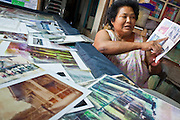 "Apr. 3, 2010 - KHUN SAMUTCHINE, THAILAND: SAMORN KHENGSAMUT is the head of the village of Khun Samutchine with some of the photos of the village she knew 30 years ago. She has made it her mission to let people know what is happening in the village. She said she has been forced to move eight times because of rising sea levels. She said, ""It's (climate change and rising sea levels) here now but in a few years it will be in Bangkok. What will happen then?"" Rising sea levels brought about by global climate change threaten the future of Khun Samutchine, a tiny fishing village about 90 minutes from Bangkok on the Gulf of Siam. The coastline advances inland here by about 20 metres (65 feet) per year causing families to move and threatening the viability of the village. The only structure in the village that hasn't moved, their Buddhist temple, is completely surrounded by water and more than 2 kilometers from the village. The temple and the village have asked the Thai government and several NGOs for help, but the only help so far is a narrow concrete causeway the government is building that will allow people to walk into the temple from a boat landing two miles away.  The walk to the village from a closer boat landing is shorter, but over an unimproved mud flat that is nearly impassible in the rainy season.  PHOTO BY JACK KURTZ"