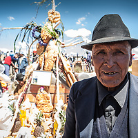 An elderly man in a black hat stands by a grave on the day of the dead in the Bolivian altiplano