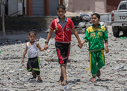 © Licensed to London News Pictures. 17/07/2014. Gaza.   <br /> Young children walk hand in hand as they look at the remains of the home of the Al Yasje family which was destroyed in an Israeli airstrike in the Jabalaya district of Gaza.     Photo credit: Alison Baskerville/LNP