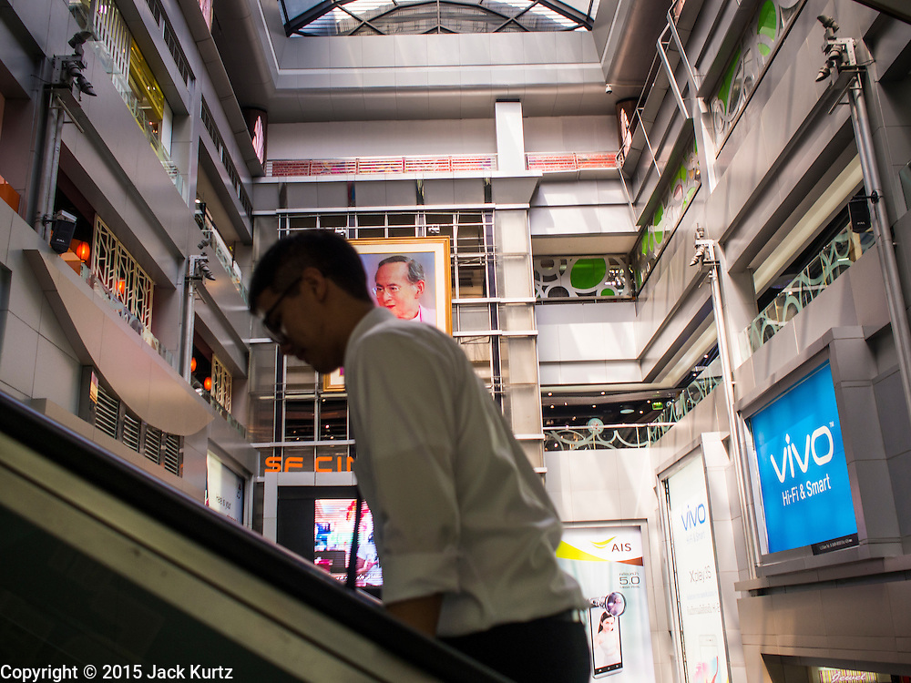 02 FEBRUARY 2015 - BANGKOK, THAILAND:  A shopper on the escalator in the central court of MBK, a large shopping mall in Bangkok. After months of relative calm following the May 2014 coup, tensions are increasing in Bangkok. The military backed junta has threatened to crack down on anyone who opposes the government. Relations with the United States have deteriorated after Daniel Russel, the US Assistant Secretary of State for Asian and Pacific Affairs, said that normalization of relations between Thailand and the US would depend on the restoration of a credible democratically elected government in Thailand.        PHOTO BY JACK KURTZ